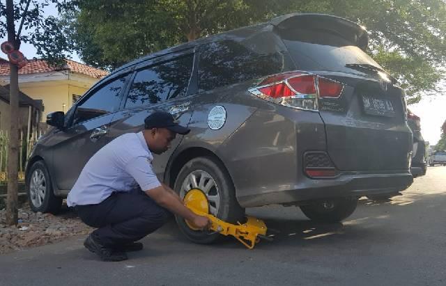 Petugas Dishub Makassar menggembok mobil yang terparkir liar di Jalan Pengayoman Makassar, Rabu (15/5/2019).