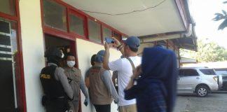 Anggota polisi yang sedang berjaga di depan pintu ruangan yang sedang digeledah.