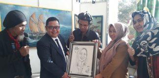 Pemberian cendera mata kepada Kepala Dinas Pariwisata Kota Makassar, Rusmayani Madjid oleh seniman karikatur, Faisal Uwa di Hotel Aryaduta Makassar, Selasa (13/8/2019). (BERITA.NEWS/Ratih Sardianti Rosi).