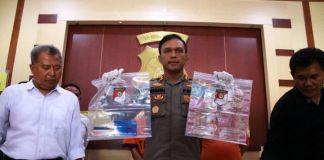 Kapolres Ngawi AKBP Pranatal Hutajulu memperlihatkan sejumlah barang bukti kasus pemerasan dengan modus postingan foto bugil di media sosial. (FOTO KOMPAS.COM)