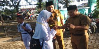 Kepala MTsN Gowa, Zulfikah Nur memantau langsung penggunaan absensi berbarkode didampingi salah seorang guru TIK, Marwan. (Foto: BERITA.NEWS/Putri).