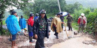 Tampak aparat Kecamatan dan desa serta warga setempat gotong royong bersihkan material longsor yang menutup jalan. (Foto: BERITA.NEWS/Putri).