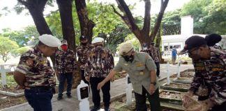 Plt Ketua FKPPI Sulsel Suwandi mahendra seragam coklat taburkan bunga ke makam pahlawan. (Foto: Istimewa).